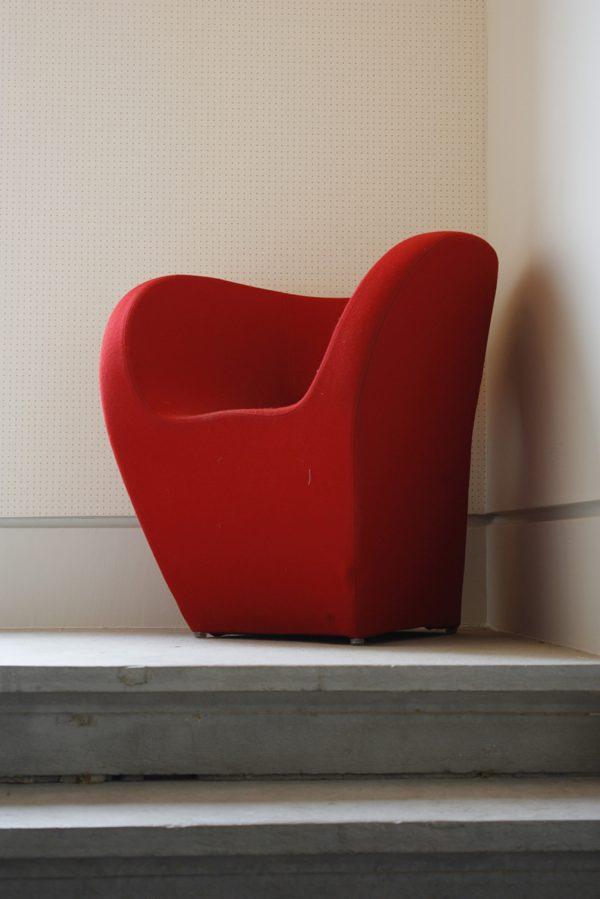 Un fauteuil rouge, installé sur le palier de l'escalier en pierre